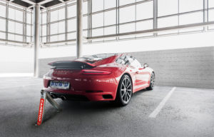 Red Porsche being protected by Cartop parking barriers
